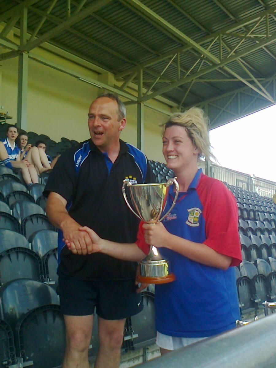 CarrigOwn Captain Caoimhe O' Callaghan receiving Munster Intermediate 7s trophy from Munster Vice Chairman Anthony O' Brien